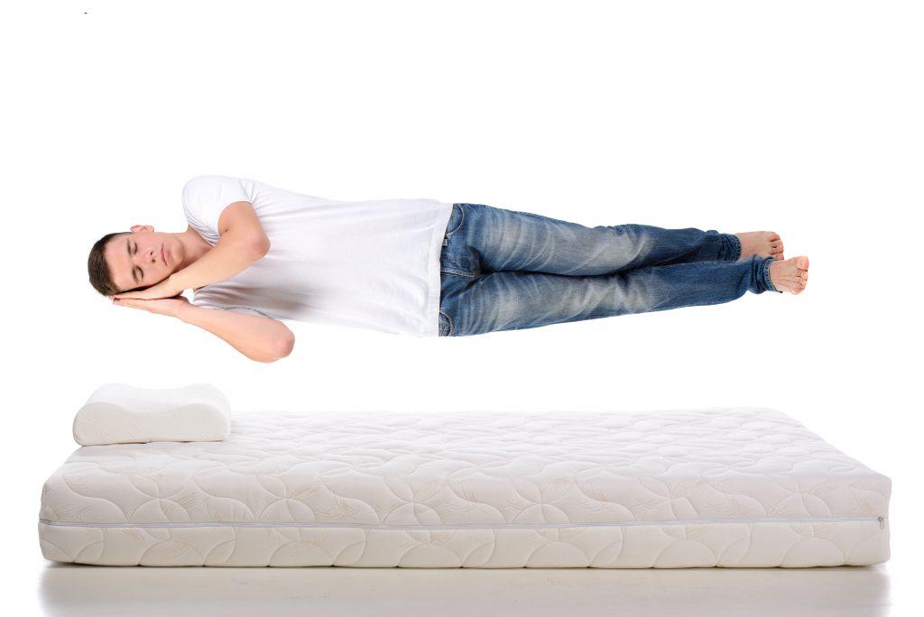 Young man sleeping on a mattress flying during sleep.